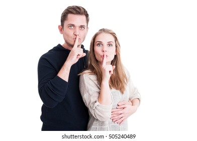 Cute couple making shush gesture with index finger isolated on white background with copy text space
