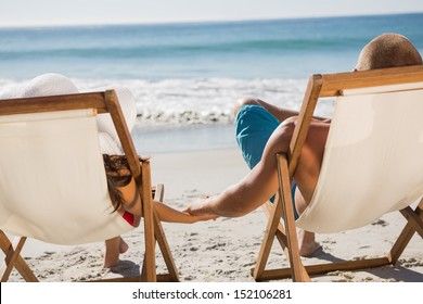 Cute couple on the beach holding hands while lying on their deck chairs
