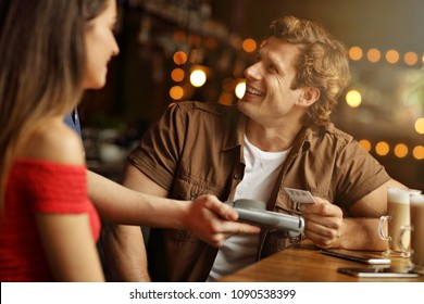 Cute couple on a date at the cafe paying by credit card