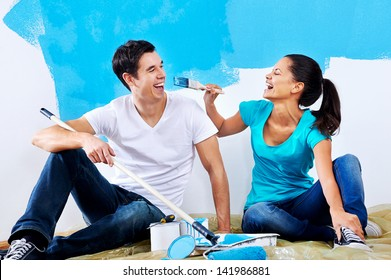 cute couple painting new home together portrait while sitting on wooden floor