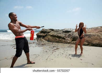 a cute couple play with a fire extinguisher on the beach