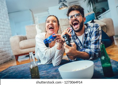Cute couple playing video games at home