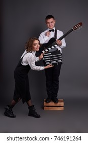 Cute couple posing in classic clothes with guitar