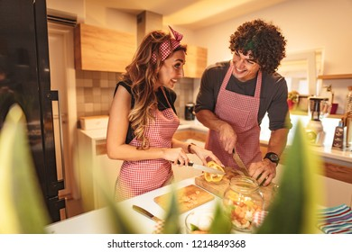 Cute couple is putting vegetables in a jar and smiling while making pickle in kitchen at home