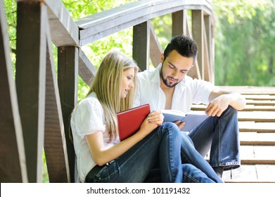 Cute couple reading boot while sitting on a wooden bridge outdoors