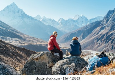 Cute Couple resting on the Everest Base Camp trekking route near Dughla 4620m. Man smiling to woman.Backpackers left Backpacks and trekking poles and enjoying valley view with Ama Dablam 6812m peak