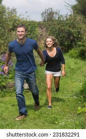 Cute couple running holding hands at home in the garden