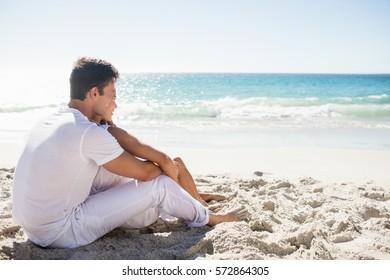 Cute couple sitting down on the beach