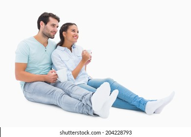 Cute couple sitting having coffee on white background