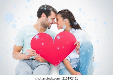 Cute couple sitting holding red heart against snow falling