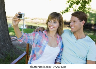 Cute couple sitting on bench in the park taking a selfie on a sunny day