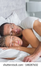 Cute couple sleeping and spooning in bed at home in bedroom
