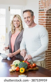 Cute couple slicing vegetables in the kitchen