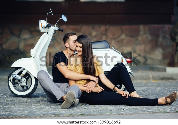 Cute couple with their scooter on a sunny day in the city