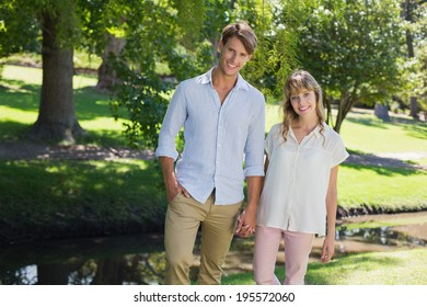 Cute couple walking hand in hand in the park smiling at camera on a sunny day