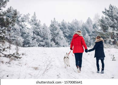 Cute couple in a winter park. Woman palying with a dog. Lady in a black jacket