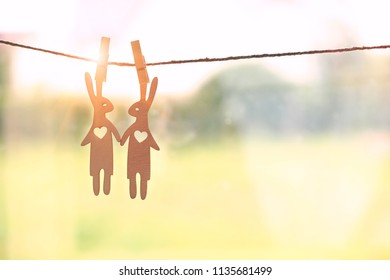 Cute couple of wooden hares in love hanging on rope with pin. Symbol of love and romance
