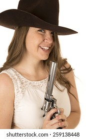 Cute cowgirl holding big pistol looking forward