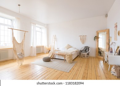 cute cozy light interior design of the apartment with a free layout of the kitchen and bedroom areas. a lot of windows, a wooden floor and a hanging swing.