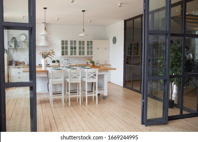 Cute cozy light interior design of the kitchen with a big window and a wooden floor. A kitchen island with white bar stools and a wooden table top is in the foreground. Glass partitions.