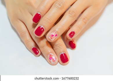Cute crack shell decorated on woman ring finger with dark pink polish painting shiny silver glitter