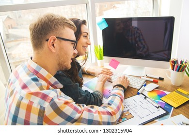 Cute creative designers working on new project in modern office