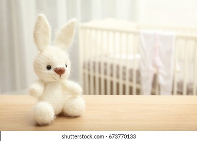 Cute crochet bunny baby toy on table in bedroom