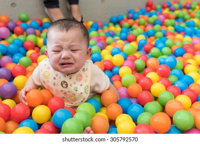 A cute crying girl sitting in a colorful ball pit at a playground.