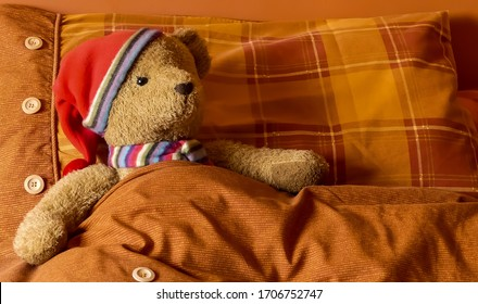 Cute, cuddly plush bear with woollen scarf & bed cap, tucked up in bed, with red and orange plaid pillow, with decorative buttons and ribbing. Interior landscape image with space for copy. England.