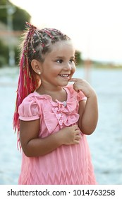 Cute curious little tanned girl with colored braids hairdo wearing a pink dress the summer beach