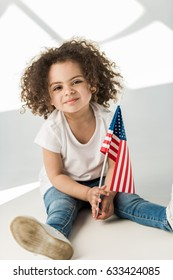 Cute curly african american baby girl with waving american flag