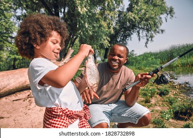 Cute curly Afro-American boy looking at the fish in his hands while his dad holding a fishing rod