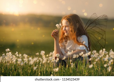 Cute curly baby dreaming on meadow outdoors. Healthy, lifestyle, happy childhood concept.