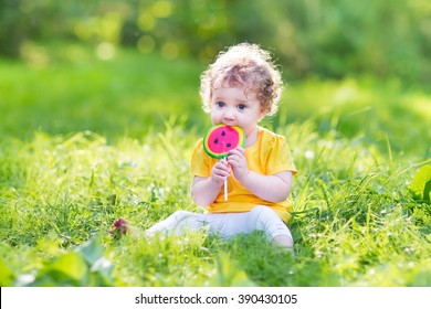 Cute curly baby girl eating watermelon candy in a sunny park