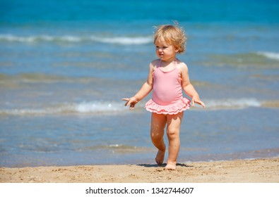 Cute curly baby girl playing on a beautiful tropical beach wearing a cute swimsuit and sunglasses