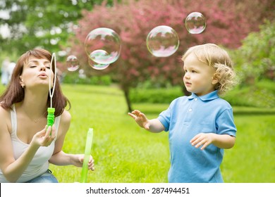 Cute curly baby with soap bubbles children playing running Child playing outdoors in the flowering trees in spring summer garden.  Springtime or summertime. Boy in spring summer landscape background.