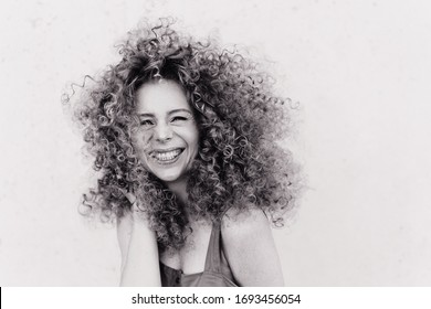 Cute curly blonde with afro hairstyle laughs. plain gray background. emotional photo black and white photo