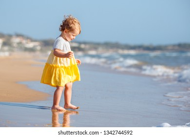Cute curly blonde baby girl wearing yellow dress playing on a beautiful tropical beach