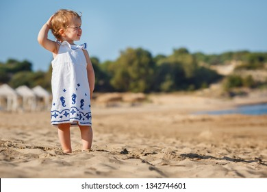 Cute curly blonde baby girl playing on a beautiful tropical beach wearing a white dress