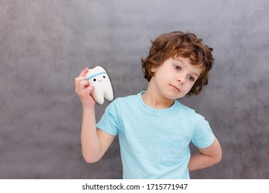 cute curly boy holds big tooth. The concept of children's health, medicine.