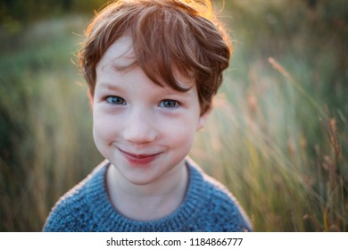Cute curly boy, a sly look at the camera, close-up portrait.