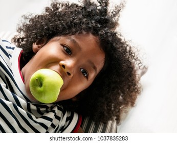 Cute curly hair boy eating an apple