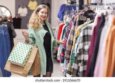 Cute curly hair woman chooses clothes in a clothing store. Portrait of nice smiling lady that find something on sale in clothes store. shopping, fashion, sale concept