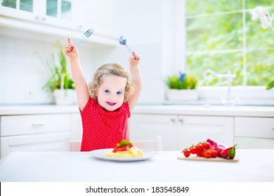 Cute curly laughing toddler girl in a red shirt playing with fork and spoon eating spaghetti with tomato sauce and vegetables for healthy lunch sitting in a white sunny modern kitchen with big window