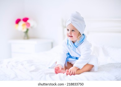 Cute curly little girl in a white and blue bathrobe with a towel over her wet hair siting in a sunny bedroom after shower or bath