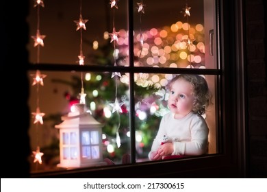 Cute curly toddler girl sitting with a toy bear at home during Christmas time, preparing to celebrate Xmas Eve, view through a window from outside into a decorated dining room with tree and lights