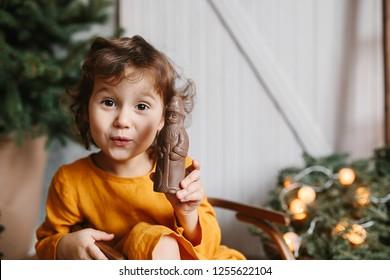 Cute curly toddler girl wearing mustard linen dress in studio near christmas tree with chocolate St Nicholas. Minimalistic stylish scandinavian christamas decoration.