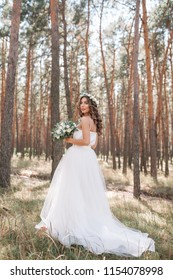 A cute curly woman in a white wedding dress with a wedding bouquet and wreath in her hair standing back to the camera in nature. Concept escaped bride. Forward to a happy bright future Runaway.