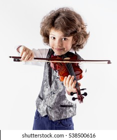 Cute curly-haired boy in a waistcoat playing the violin leaning forward. Close-up. Gray background.