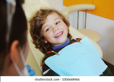 A cute, curly-haired child indulges and grimaces in a dental chair